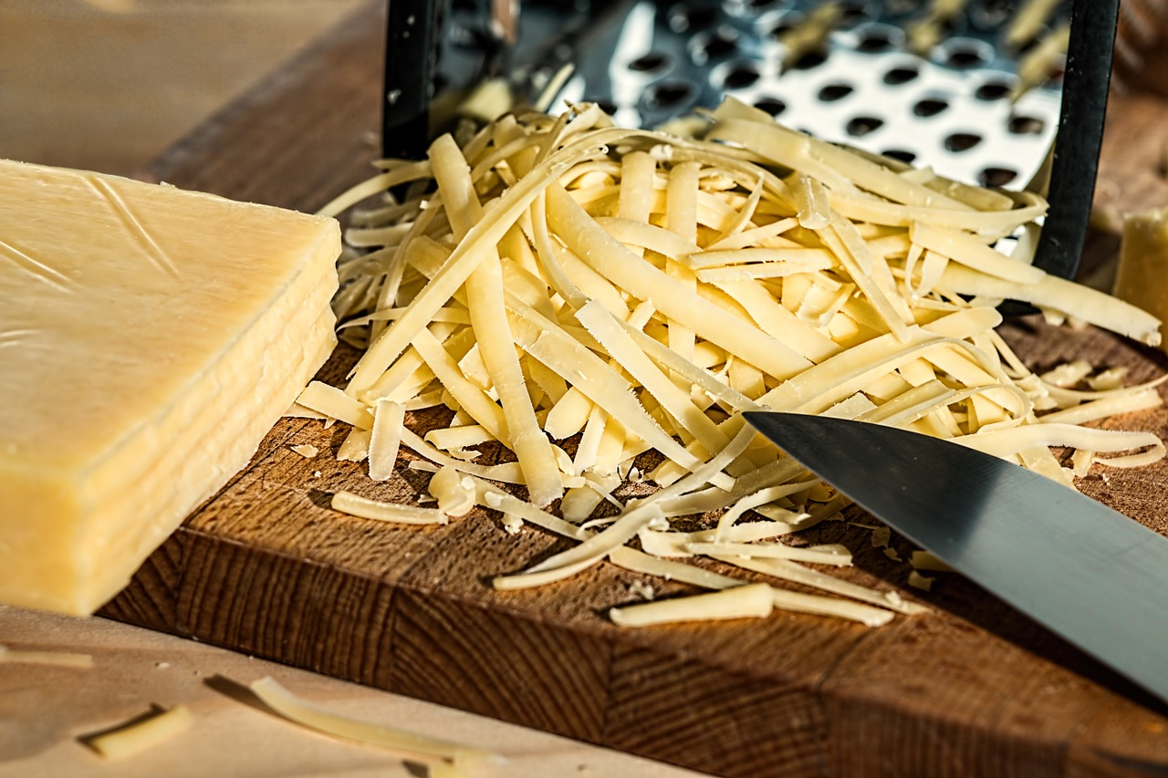 grated cheese next to a knife on a chopping board